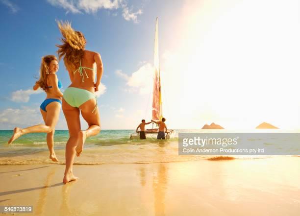 Women running on beach to sailboat in ocean