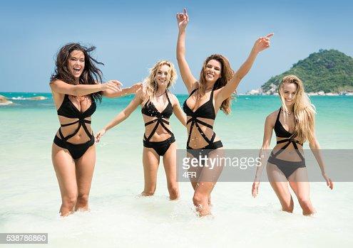 Women running, splashing in the Ocean on Vacation