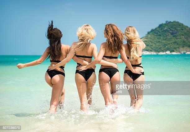 Women running, splashing into the Ocean on Vacation