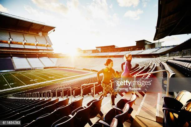 Women running stairs together in stadium at sunset