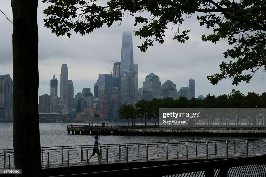 A women runs on a pier in Hoboken, NJ as a morning fog lifts over One World Trade Center and Lower Manhattan on May 30, 2016 in New York City.