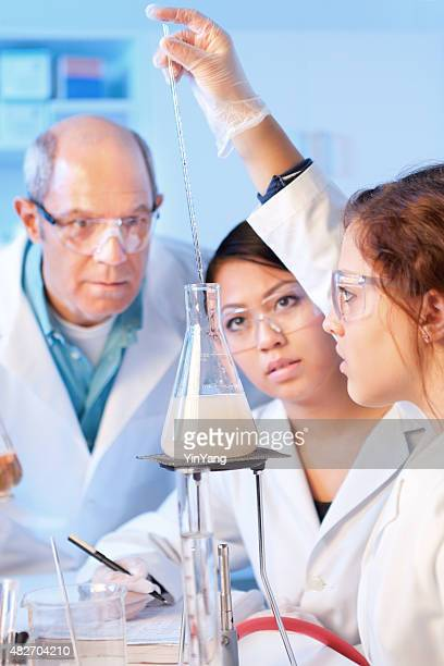 Women Science Students Studying Chemistry with Professor in Laboratory