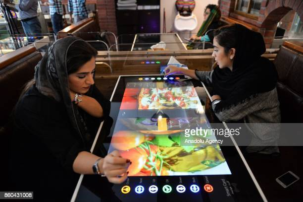 Women select their food served by robot waiter which moves on rail system placed between tables at the first robotic restaurant 'RoboChef' in Tehran...