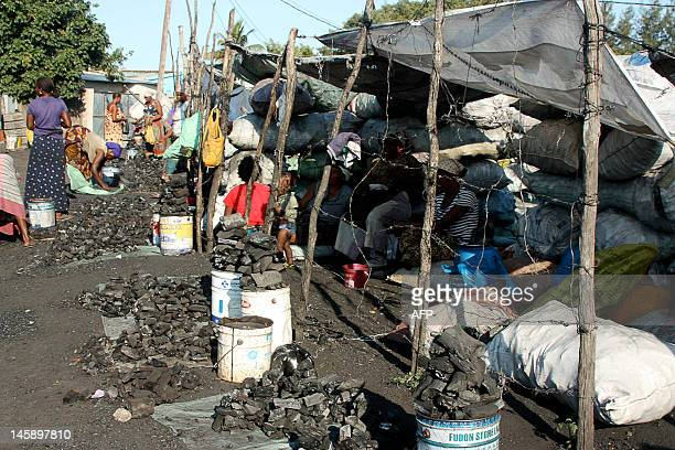 Women sell charcoal at the Xipamanine charcoal market one of hundreds of its kind tucked deep inside the sprawling shantytowns that ring the...