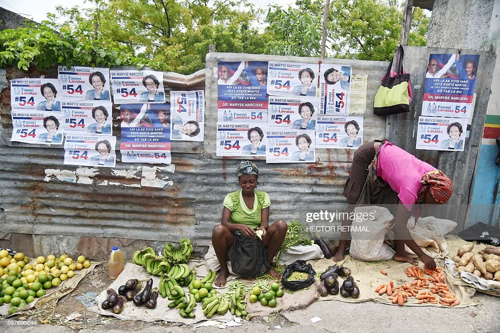 Women sell vegetables in a street beside electoral posters of Presidential Candidate from Lavalas Political Party Maryse Narcisse in PortauPrince on...