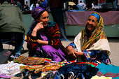 Women selling fabrics at a market in Urganch Uzbekistan along the Silk Road
