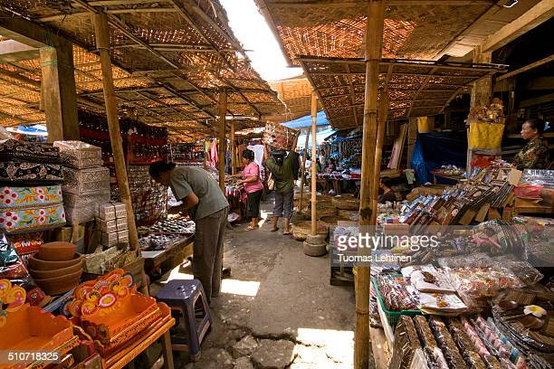 Women selling souvenirs art craft and other products at a shaded market in Ubud Bali Indonesia