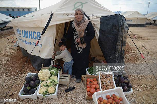 ZA'ATARI JORDAN JANUARY 30 A women sells vegetables and fruit from her tent in as Syrian refugees go about their daily business in the Za'atari...