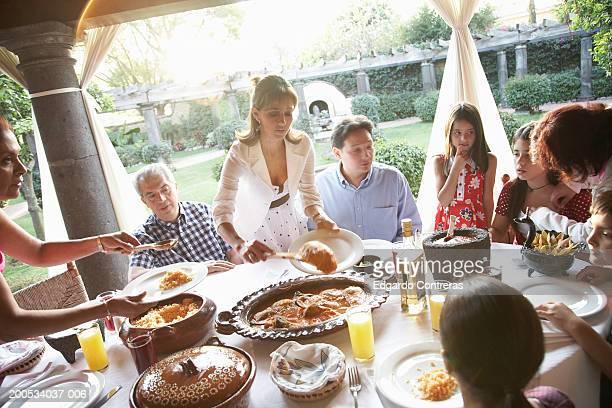 Women serving family dinner on patio