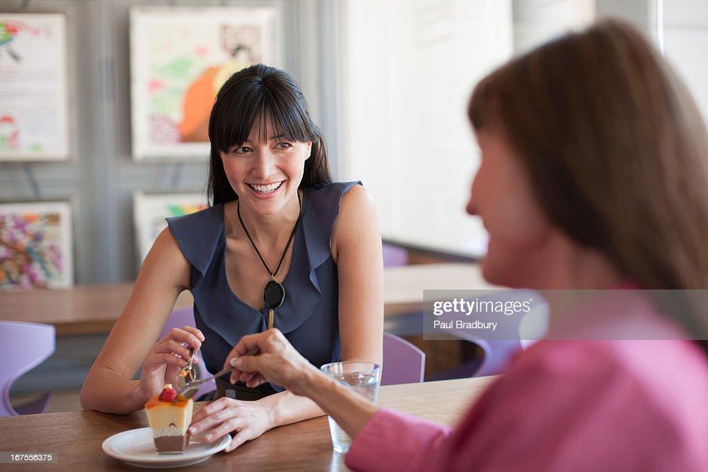 Women sharing dessert in cafe