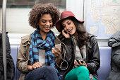 Women sharing earphones on subway