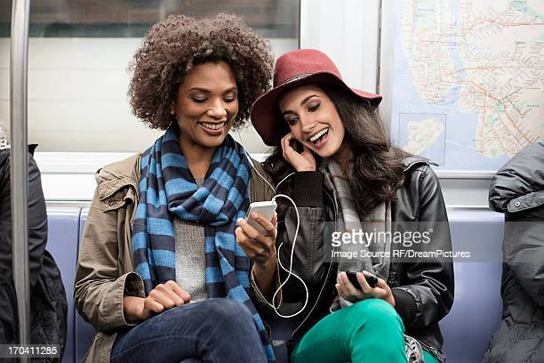 Women sharing earphones on subway