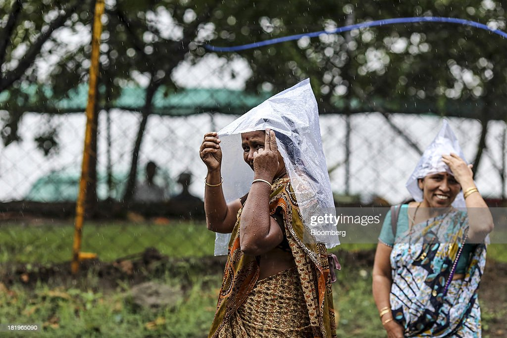 Women shelter their heads from the rain outside the Wockhardt Ltd. manufacturing facility in the Chikalthana industrial area in Aurangabad, India, on Monday, Sept. 16, 2013. Wockhardt currently controls about 26 percent of the U.S. market for metoprolol, a generic version of the heart pill sold by London-based AstraZeneca Plc under the brand name Toprol-XL, according to Needham & Co. Metoprolol alone makes up about 14 percent of the company's 56 billion rupees in annual revenue. Photographer: Dhiraj Singh/Bloomberg via Getty Images