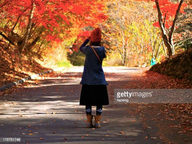 Women shooting the autumn red leaves