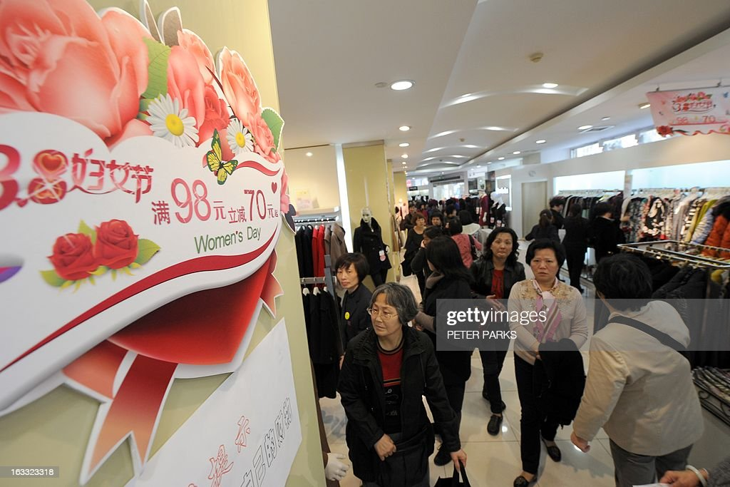 Women shop at a clothes store in Shanghai with discounts for International Women's Day on March 8, 2013. International Women's Day in China is celebrated with various events including discount shopping for women at malls in cities around China. AFP PHOTO/Peter PARKS