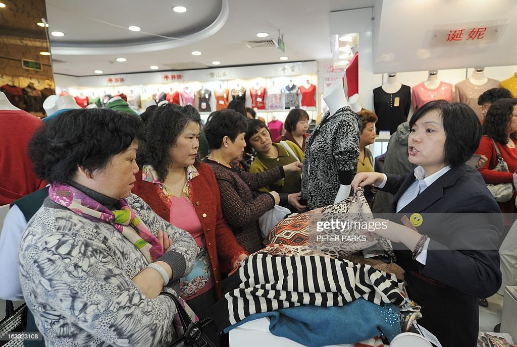 Women shop at a woman's clothes store in Shanghai with discounts for International Women's Day on March 8, 2013. International Women's Day in China is celebrated with various events including discount shopping for women at malls in cities around China. AFP PHOTO/Peter PARKS