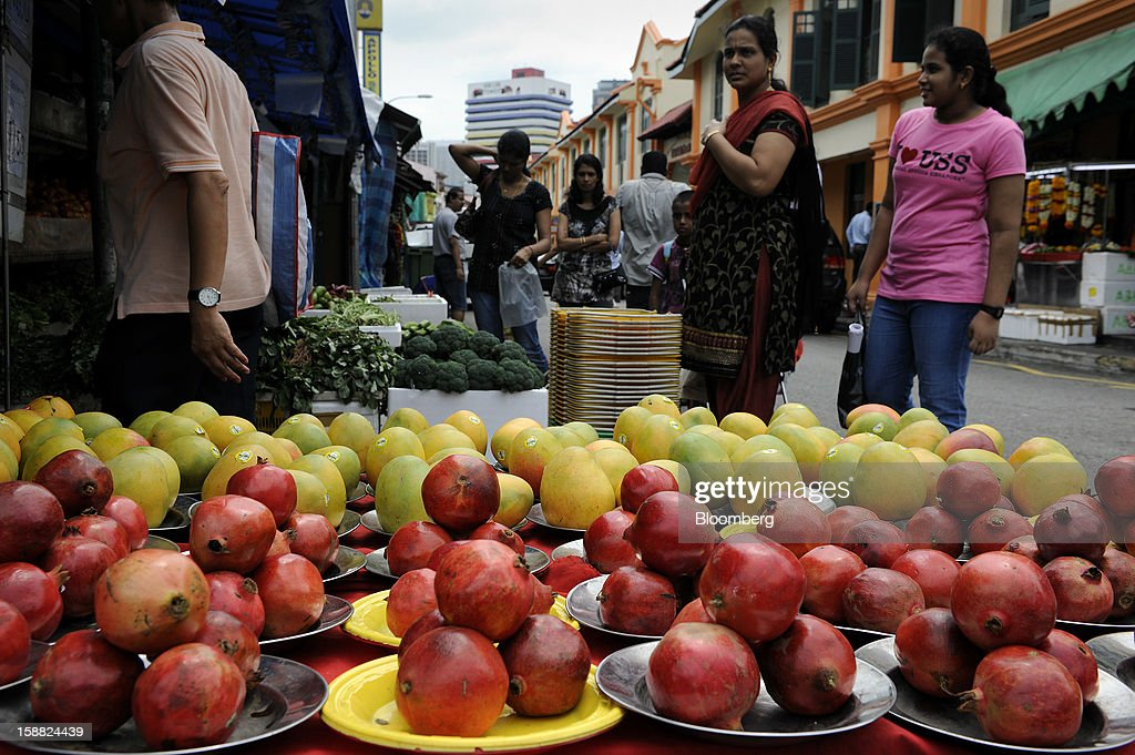Women shop for fruit in the area of Little India in Singapore, on Saturday, Dec. 29, 2012. Singapore may grapple with elevated inflationary pressures for a third year in 2013, reducing scope for the central bank to provide stimulus to an economy that probably entered a technical recession this quarter. Photographer: Munshi Ahmed/Bloomberg via Getty Images