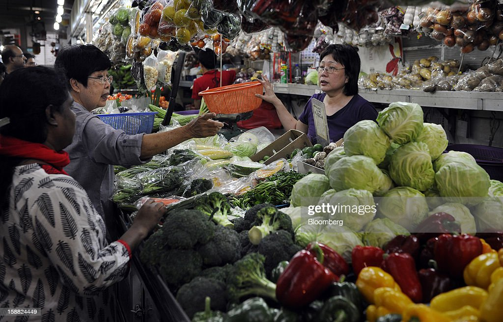 Women shop for vegetables at a market in Singapore, on Saturday, Dec. 29, 2012. Singapore may grapple with elevated inflationary pressures for a third year in 2013, reducing scope for the central bank to provide stimulus to an economy that probably entered a technical recession this quarter. Photographer: Munshi Ahmed/Bloomberg via Getty Images