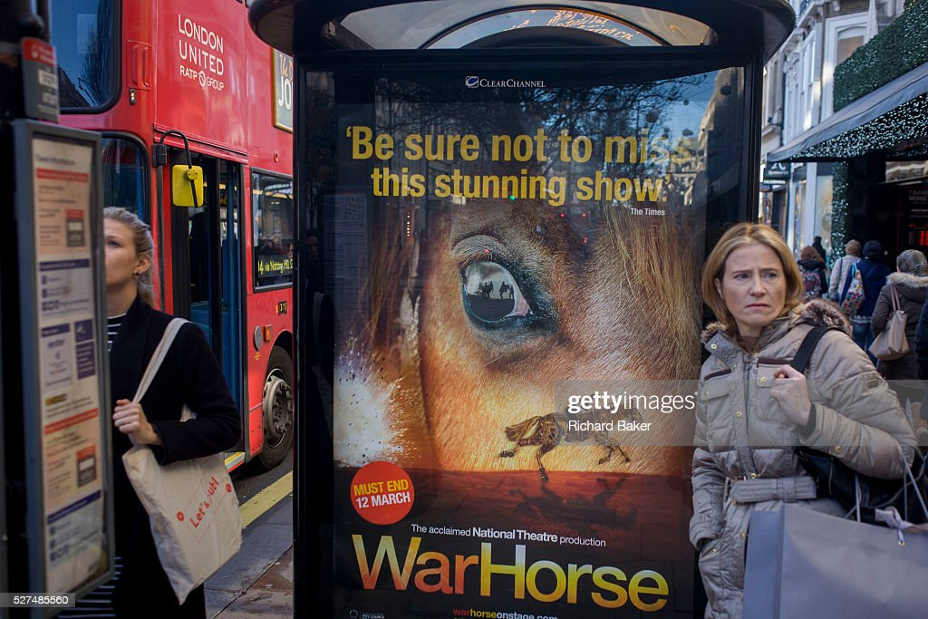 Women shoppers at a bus stop with a War Horse poster in central London The women are in the busy Oxford Street shopping street and bus stop posters...