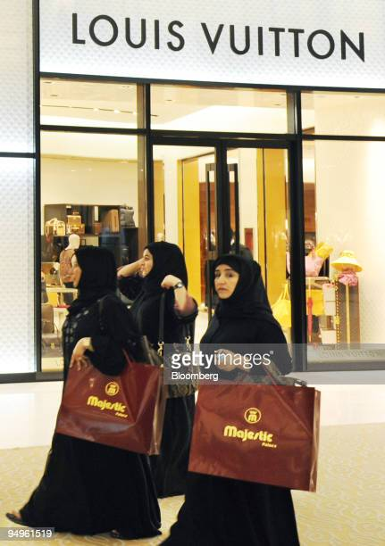Women shoppers walk past a Louis Vuitton store at the Dubai Mall which is owned by Emaar Properties PJSC in Dubai United Arab Emirates on Sunday July...