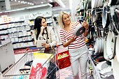 Women shopping cookware in supermarket