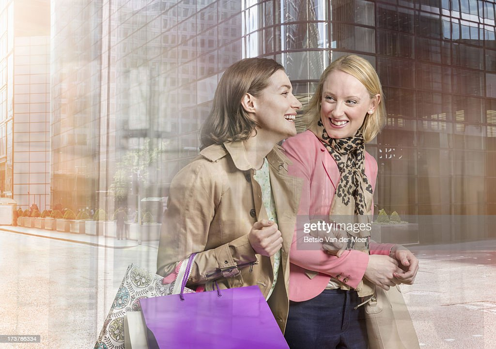 Women shopping, reflections of city through window : Stock Photo