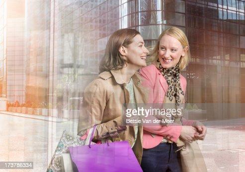Women shopping, reflections of city through window