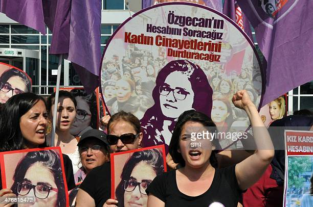 Women shout slogans in front of a banner reading during the trial of three men at a Turkish court facing life imprisonment over the murder and...