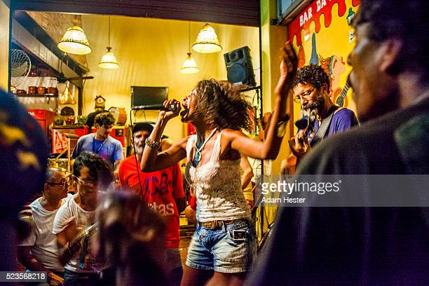 A women singing and dancing inside of a bar surrounded by people.