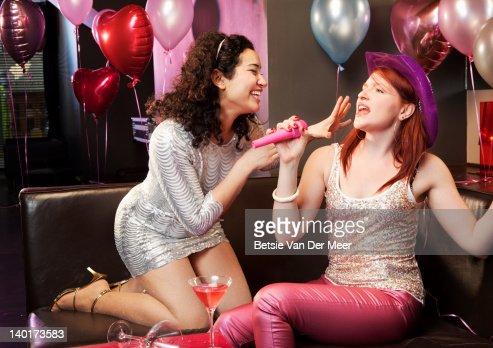 Women singing karaoke. : Stock Photo