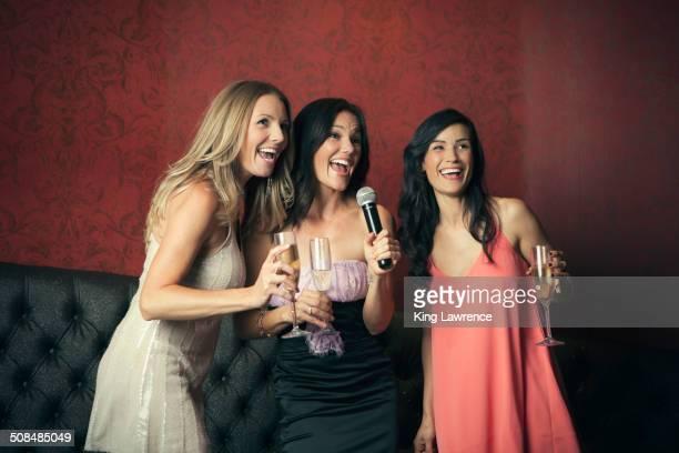 Women singing karaoke together in nightclub