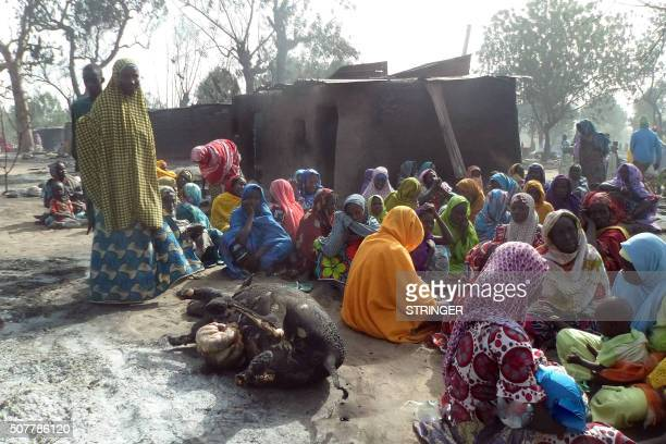 Women sit beside the burnt carcass of a cow after Boko Haram attacks at Dalori village on the outskirts of Maiduguri in northeastern Nigeria on...