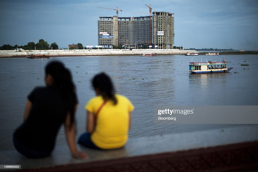 Women sit by the Tonle Sap river as a development by Sokha Hotels & Resorts, a unit of Sokimex Group, stands under construction in Phnom Penh, Cambodia, on Saturday, Nov. 17, 2012. U.S. President Barack Obama arrives in Phnom Penh later today to join the Association of Southeast Asian Nations (Asean) East Asia Summit, which also includes leaders from Japan, South Korea, India, Russia, Australia and New Zealand. Photographer: Will Baxter/Bloomberg via Getty Images