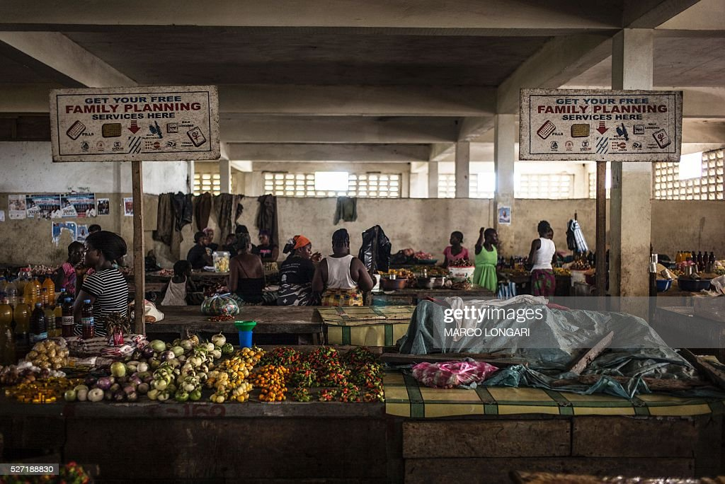 Women sit by their stalls at the Jorkpan market at Sinkor district in Monrovia, on May 2, 2016. Family planning services, like contraceptives and counselling are available in the markets in Liberia, an initiative that is aimed at tackling the high adolescent pregnancy rate in the younger population. / AFP / MARCO