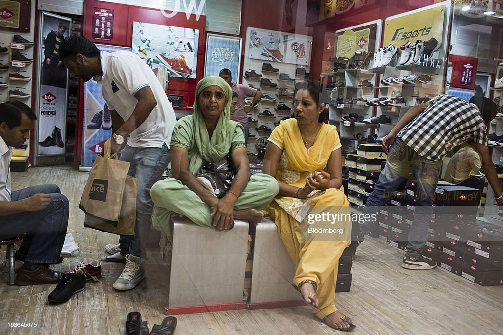 Women sit in a shoe store at the AlphaOne shopping mall in Amritsar, India, on Thursday, May 9, 2013. India's consumer price index (CPI) for April rose 9.39 percent year on year, the Central Statistics Office said in a statement on its website. Photographer: Brent Lewin/Bloomberg via Getty Images