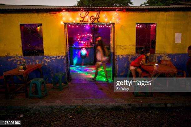Women sit in front of a small bar just meters from a busy railway track in a brothel area on August 27 2013 in Jakarta Indonesia Brothel areas are...