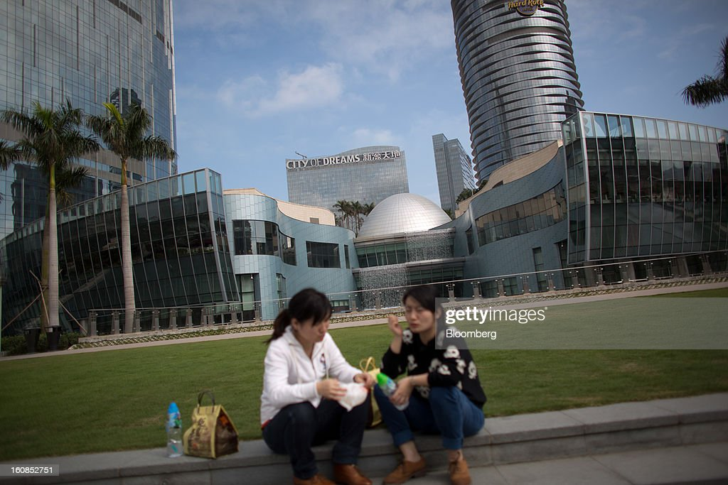 Women sit in front of the City of Dreams complex, operated by Melco Crown Entertainment Ltd., in Macau, China, on Wednesday, Feb. 6, 2013. Casino industry revenue in the gambling hub climbed 14 percent to a record 304 billion patacas ($38 billion) last year. Photographer: Lam Yik Fei/Bloomberg via Getty Images
