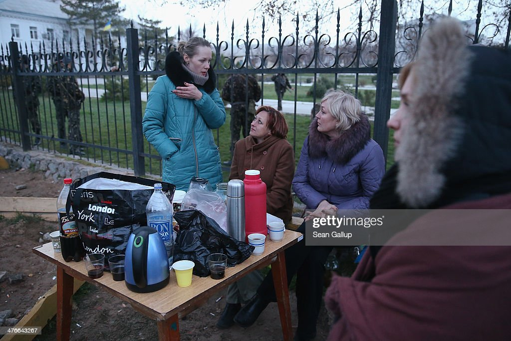 Women sit in the early morning just outside the Belbek military base on March 4, 2014 in Lubimovka, Ukraine. Tensions at the base, where between 300 and 400 Ukrainian soldiers are stationed, were high overnight as a 4pm deadline the day before reportedly given by Russian troops for the Ukrainians to surrender passed and the troops feared the Russians might attack the base overnight. Many of the soldiers have family that live in apartment blocks just outside the base and about two dozen family members braved the cold and huddled overnight with tea and cognac by a campfire outside, ready to block the road to the base entrance should the Russians appear.