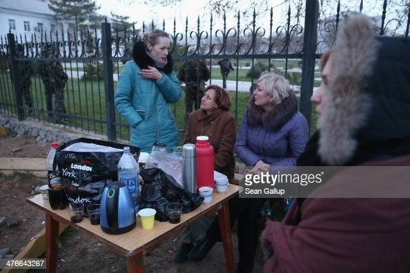 Women sit in the early morning just outside the Belbek military base on March 4 2014 in Lubimovka Ukraine Tensions at the base where between 300 and...