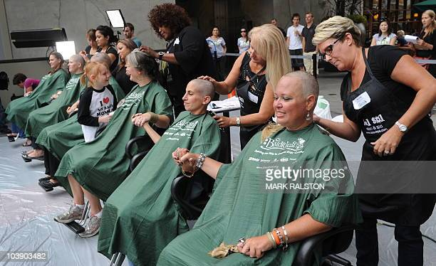 Women sit in the hairdressers chair as they join 45 other mothers getting their heads shaved to support the St Baldrick's Foundation which raises...