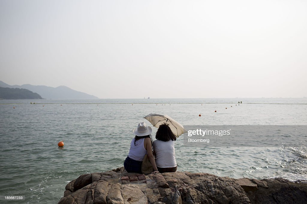 Women sit on a rock at Hung Shing Ye beach on Lamma Island in Hong Kong China on Tuesday Oct 22 2013 Hong Kong has the world's highest home prices...