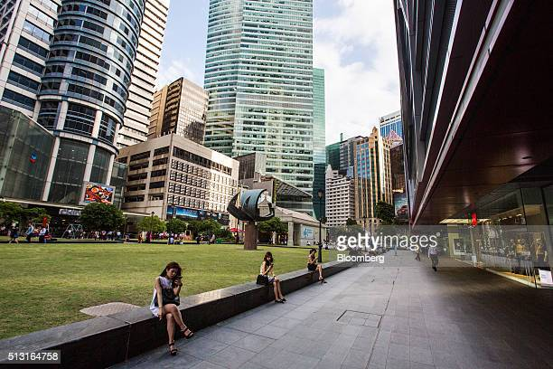 Women sit on a wall using mobile phones at Raffles Place in the central business district area of Singapore on Monday Feb 29 2016 Singapore's...
