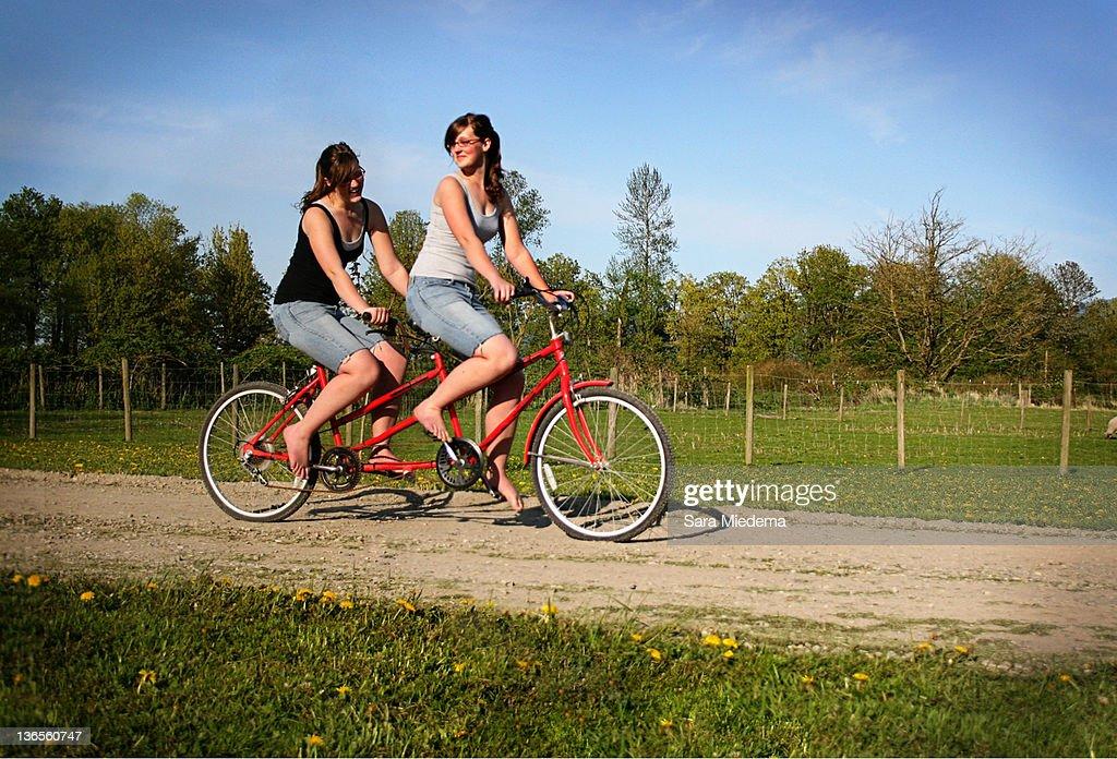 Women siting on tandem bike : Stock Photo