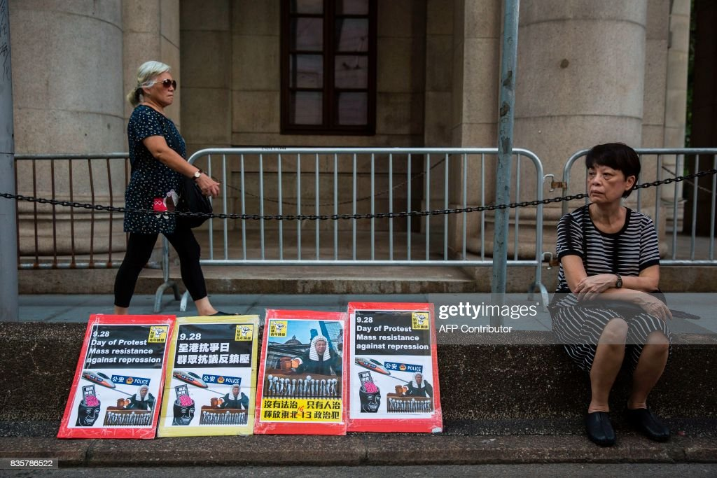 A women (R) sits next to placards outside the Court of Final appeal during a march in Hong Kong on August 20, 2017, to protest the jailing of Joshua Wong, Nathan Law and Alex Chow (not pictured), the leaders of Hong Kong's 'Umbrella Movement', after their sentencing at the High Court on August 17. Wong, Law and Chow were handed sentences of six to eight months by the Court of Appeal for their role in 2014's massive Umbrella Movement protests, which called for fully free leadership elections and were an unprecedented challenge to Beijing. /
