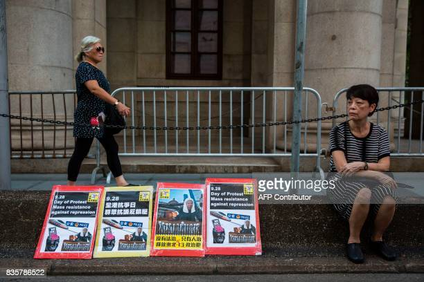 A women sits next to placards outside the Court of Final appeal during a march in Hong Kong on August 20 to protest the jailing of Joshua Wong Nathan...