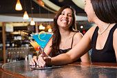 Women sitting at a bar with martinis