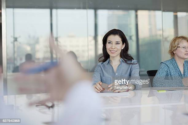 Women sitting at conference table in bright office