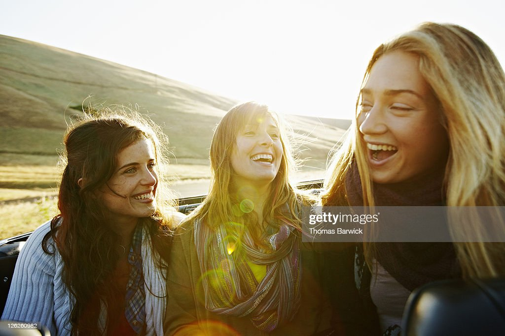 Women sitting in convertible at sunrise laughing : Stock Photo