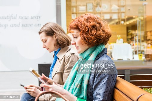 Women sitting in shopping area looking at internet : Photo