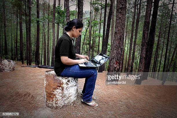 Femmes assis dans la forêt tenant un ordinateur portable